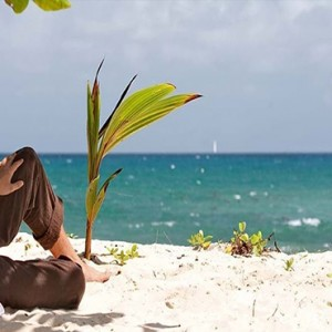 Constance Lemuria - Luxury Seychelles Honeymoon Packages - couple relaxing on beach