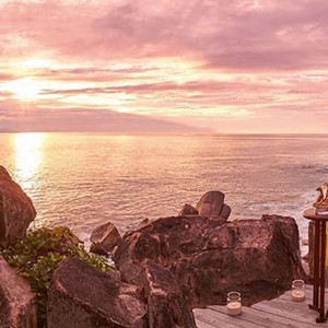 Constance Lemuria - Luxury Seychelles Honeymoon Packages - couple watching the sunset with a glass of champagne