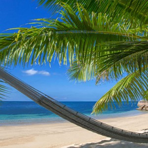 Coco de Mer & Black Parrot Suites - Luxury Seychelles Honeymoon Packages - hammock on beach