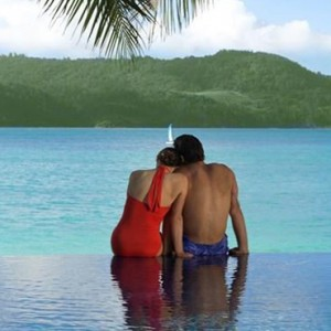 Beach Club Hamilton Islands - Australia Honeymoon Packages - couple sitting on the edge of beach club pool
