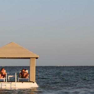Puri Santrian - Bali Honeymoon Packages - relaxing in cabana on sea