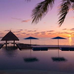 Four Seasons Resort Maldives at Kuda Huraa - Maldives Honeymoon Packages - pool at sunset