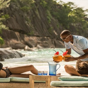 Four Seasons Resort Seychelles - Luxury Seychelles Honeymoon packages - Couple relaxing on beach