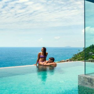 Four Seasons Resort Seychelles - Luxury Seychelles Honeymoon packages - couple in pool ocean gazing