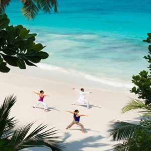 Four Seasons Resort Seychelles - Luxury Seychelles Honeymoon packages - yoga on beach