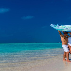 Cocoon Maldives - Luxury Maldives Honeymoon Packages - couple at beach