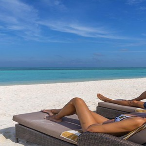 Cocoon Maldives - Luxury Maldives Honeymoon Packages - relaxing on the beach