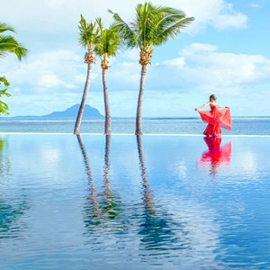 Maradiva Villas Resort & Spa - Luxury Mauritius Honeymoon Packages - woman in red dress walking by infinity pool
