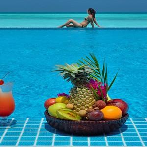 Atmosphere Kanifushi - Luxury Maldives Honeymoon Packages - Women by the pool