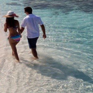 Coco Bodu Hithi - Luxury Maldives Honeymoon Packages - Couple on beach