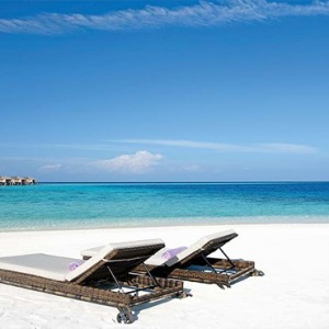 Constance Moofushi - Luxury Maldives Honeymoon Packages - Sun loungers on beach