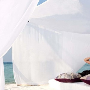 Constance Moofushi - Luxury Maldives Honeymoon Packages - Woman relaxing on beach