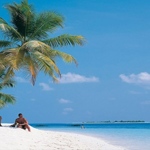 Diamonds Athuruga - Luxury Maldives Honeymoon Packages - couple on beach