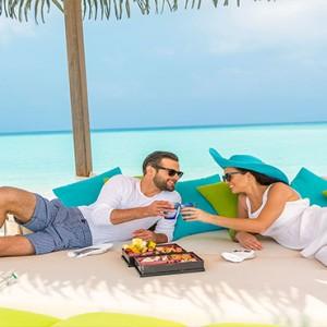 Hurawalhi Island - Luxury Maldives Honeymoon Packages - couple having beach picnic