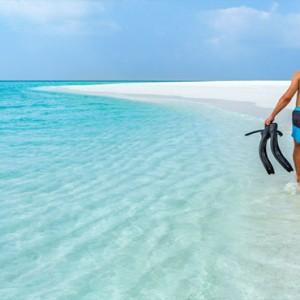 Hurawalhi Island - Luxury Maldives Honeymoon Packages - couple on beach snorkelling