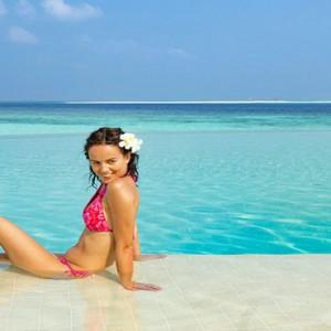 Hurawalhi Island - Luxury Maldives Honeymoon Packages - women by pool