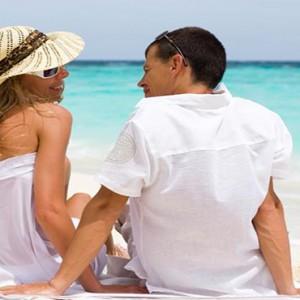 JA Manafaru - Luxury Maldives honeymoon packages - Couple on the beach