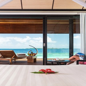 Lily Beach Resort and Spa at Huvahendhoo - Luxury Maldives Honeymoon Packages - Lagoon Villa women relaxing in resort