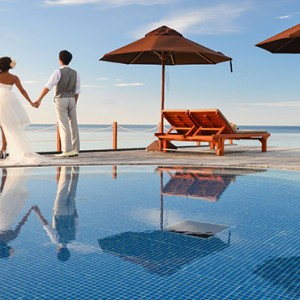 Lily Beach Resort and Spa at Huvahendhoo - Luxury Maldives Honeymoon Packages - wedding couple by pool