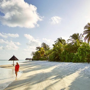 Lux South Ari Atoll - Luxury Maldives Honeymoon Packages - Woman taking a stroll on beach