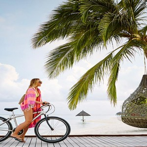 Lux South Ari Atoll - Luxury Maldives Honeymoon Packages - woman cycling