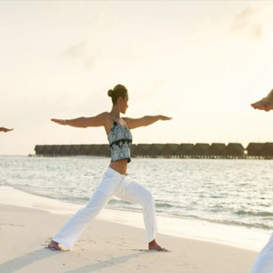 Lux South Ari Atoll - Luxury Maldives Honeymoon Packages - yoga on the beach