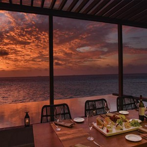 Ozen by Atmosphere at Maadhoo Island - Luxury Maldives Honeymoon Packages - OZEN Water suite exterior dining at sunset