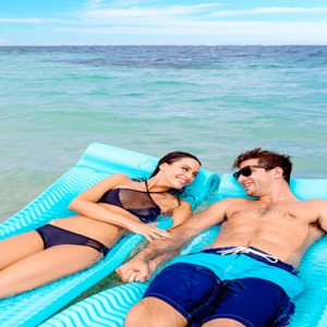 Serenity at Coconut Bay - Luxury St lucia Honeymoon Packages - Couple floating in sea