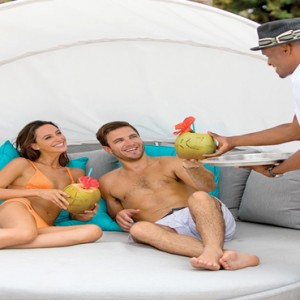Serenity at Coconut Bay - Luxury St lucia Honeymoon Packages - couple relaxing on day bed
