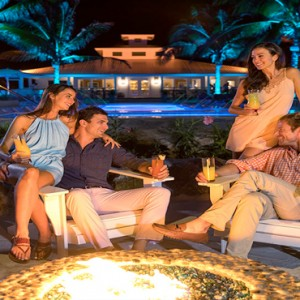 Serenity at Coconut Bay - Luxury St lucia Honeymoon Packages - couples by firepit having drinks