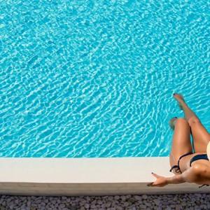 Sun Aqua Vilu Reef - Luxury Maldives honeymoon packages - Woman by the pool