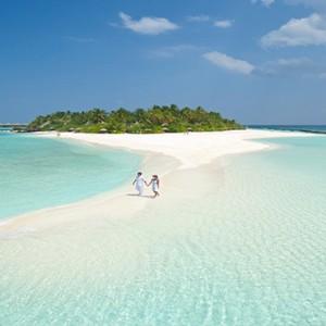 Sun Aqua Vilu Reef - Luxury Maldives honeymoon packages - couple strolling on Sandbank