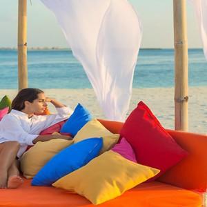 Sun Aqua Vilu Reef - Luxury Maldives honeymoon packages - woman relaxing on the beach