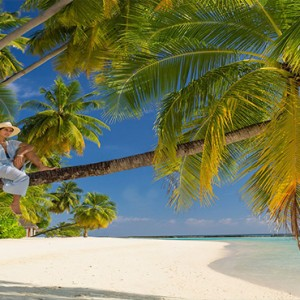 Sun Aqua Vilu Reef - Luxury Maldives honeymoon packages - women on tree on beach