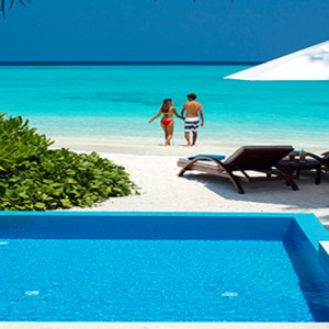 Velassaru Maldives - Luxury Maldives Honeymoon Packages - Beach Villa with pool couple on beach