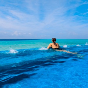 Velassaru Maldives - Luxury Maldives Honeymoon Packages - woman in main infinity pool