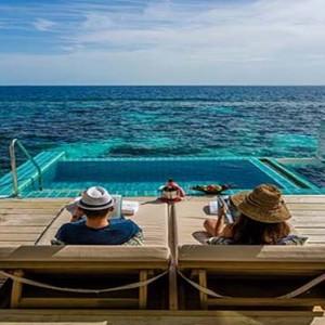 Centara Grand Island Resort & Spa - Luxury Maldives Honeymoon Packages - Sunset Ocean Pool Villa couple lounging on deck