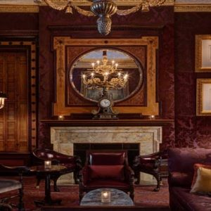 New York Honeymoon Packages Lotte New York Palace Living Space With Wooden Accents, Warm Red Decor & Fireplace